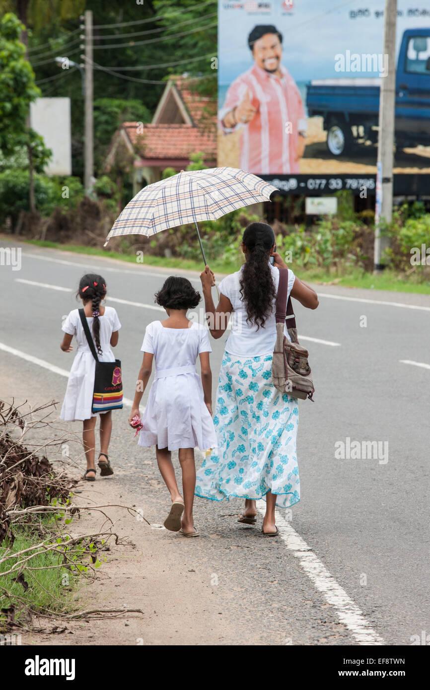 Local family walking alongside a rural road on a school run. Walking to school. At Tissa,Tissamaharama,Sri Lanka.Umbrella - Stock Image