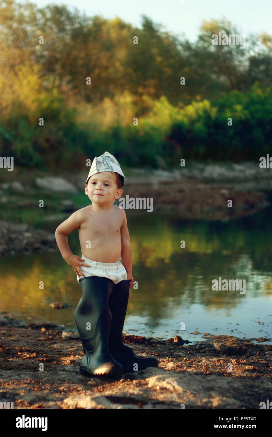 Boy (18-23 months) wearing huge rubber boots and paper hat standing by pond Stock Photo