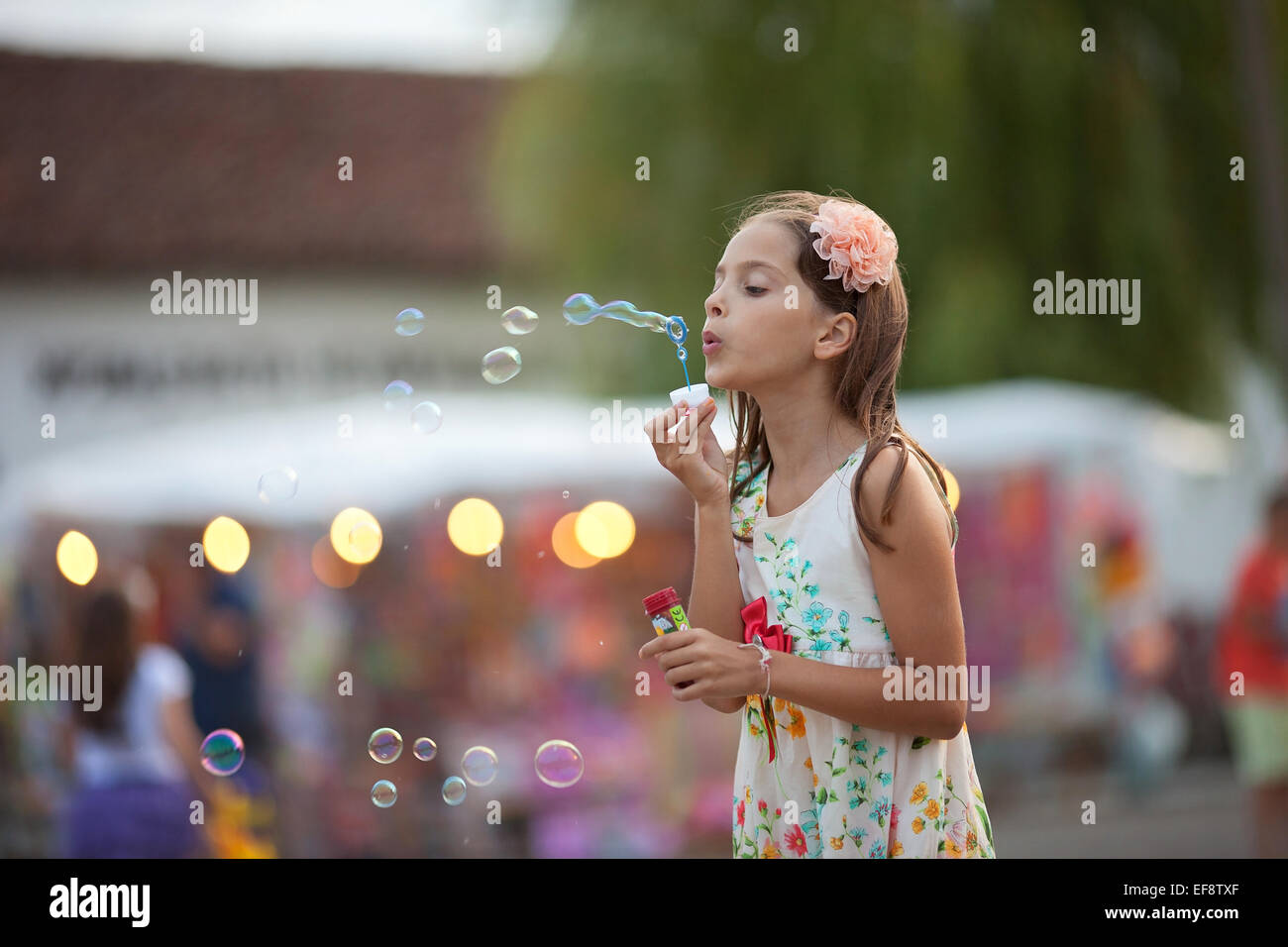 Girl (8-9) in dress blowing soap bubbles Stock Photo