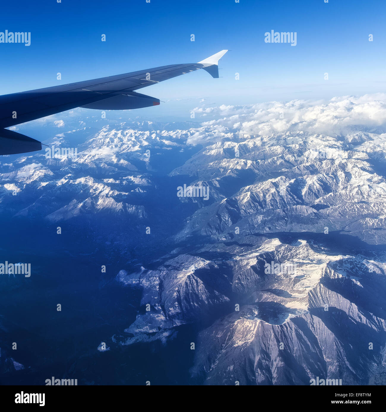 France, Alps, Aerial view of snowcapped mountain landscape and airplane wing - Stock Image