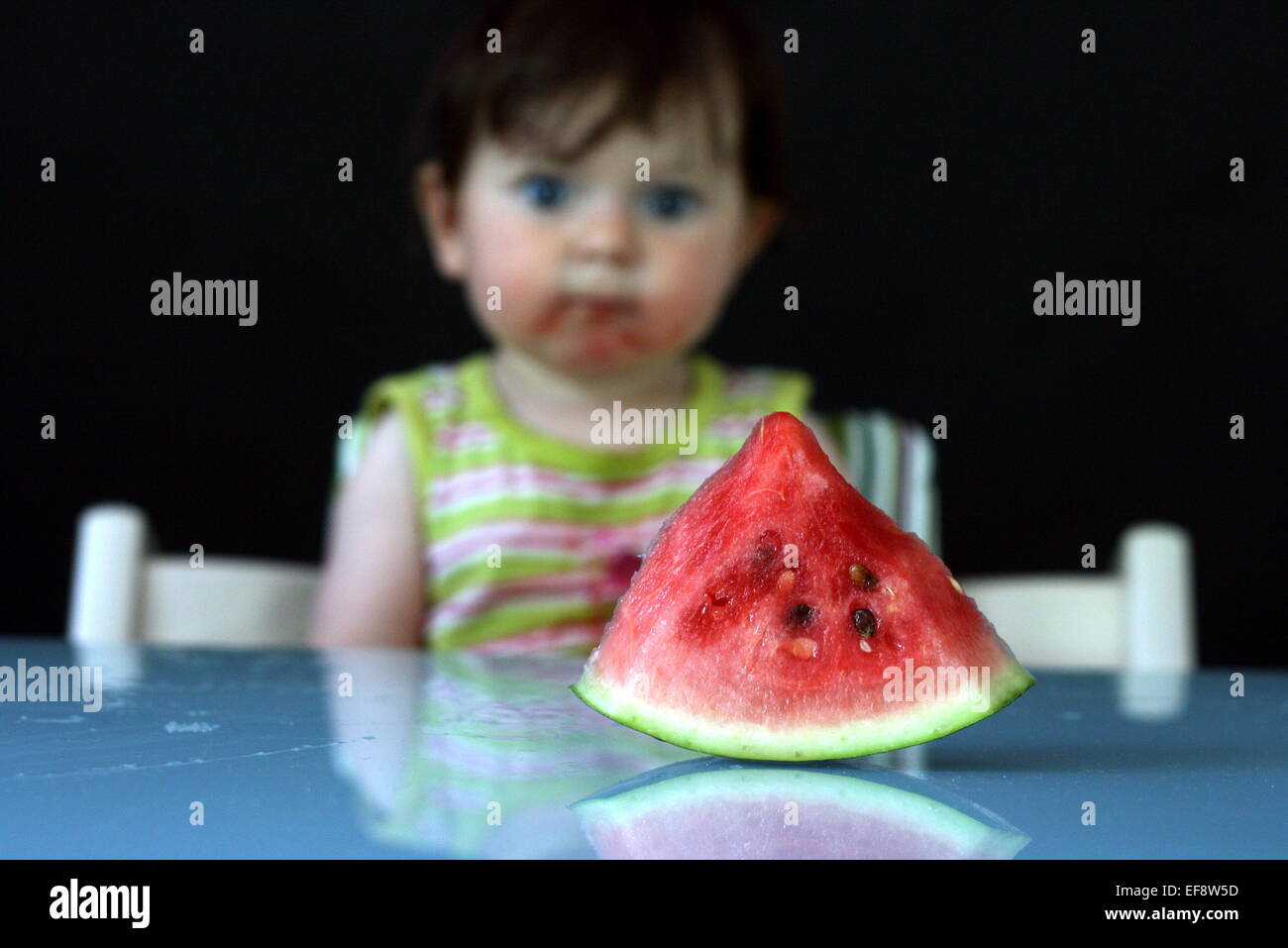 Watermelon slice and baby girl (6-11 months) on background - Stock Image