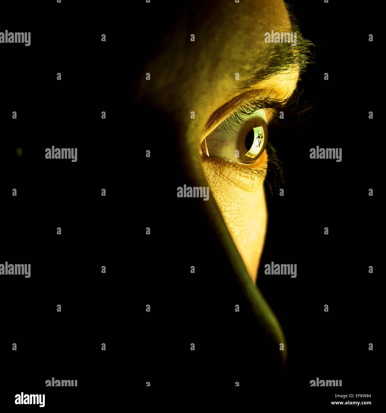 Close-up of eye with reflection of hazard symbol - Stock Image