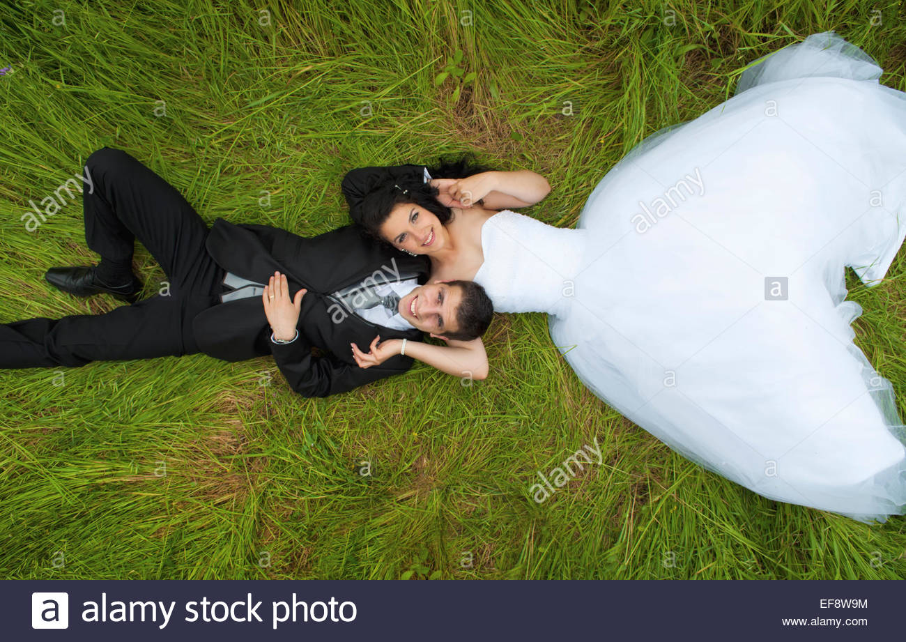 Bride and groom lying on grass Stock Photo