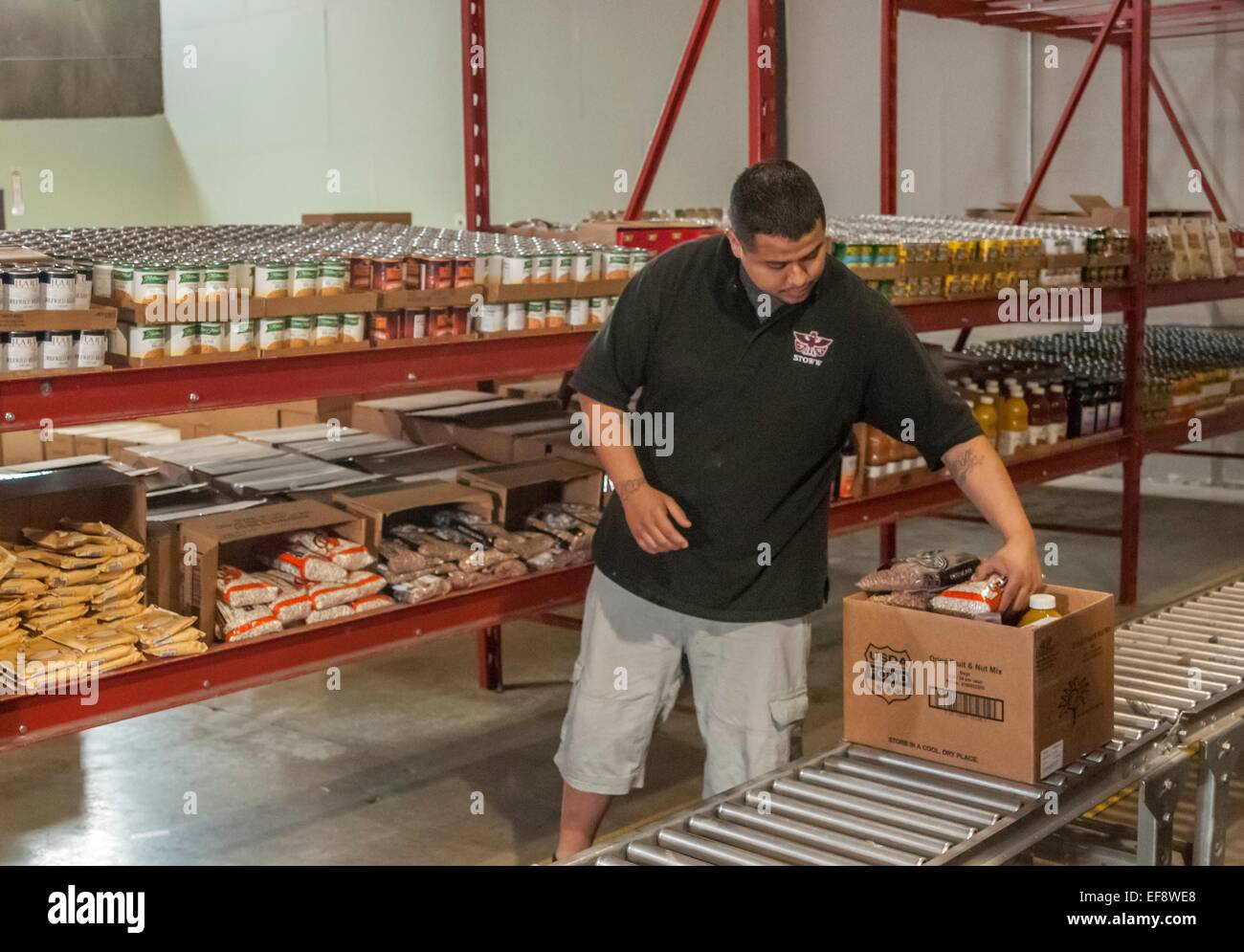 David Gibson an employee of the Food Distribution Program on Indian Reservations fills requests at the food distribution - Stock Image