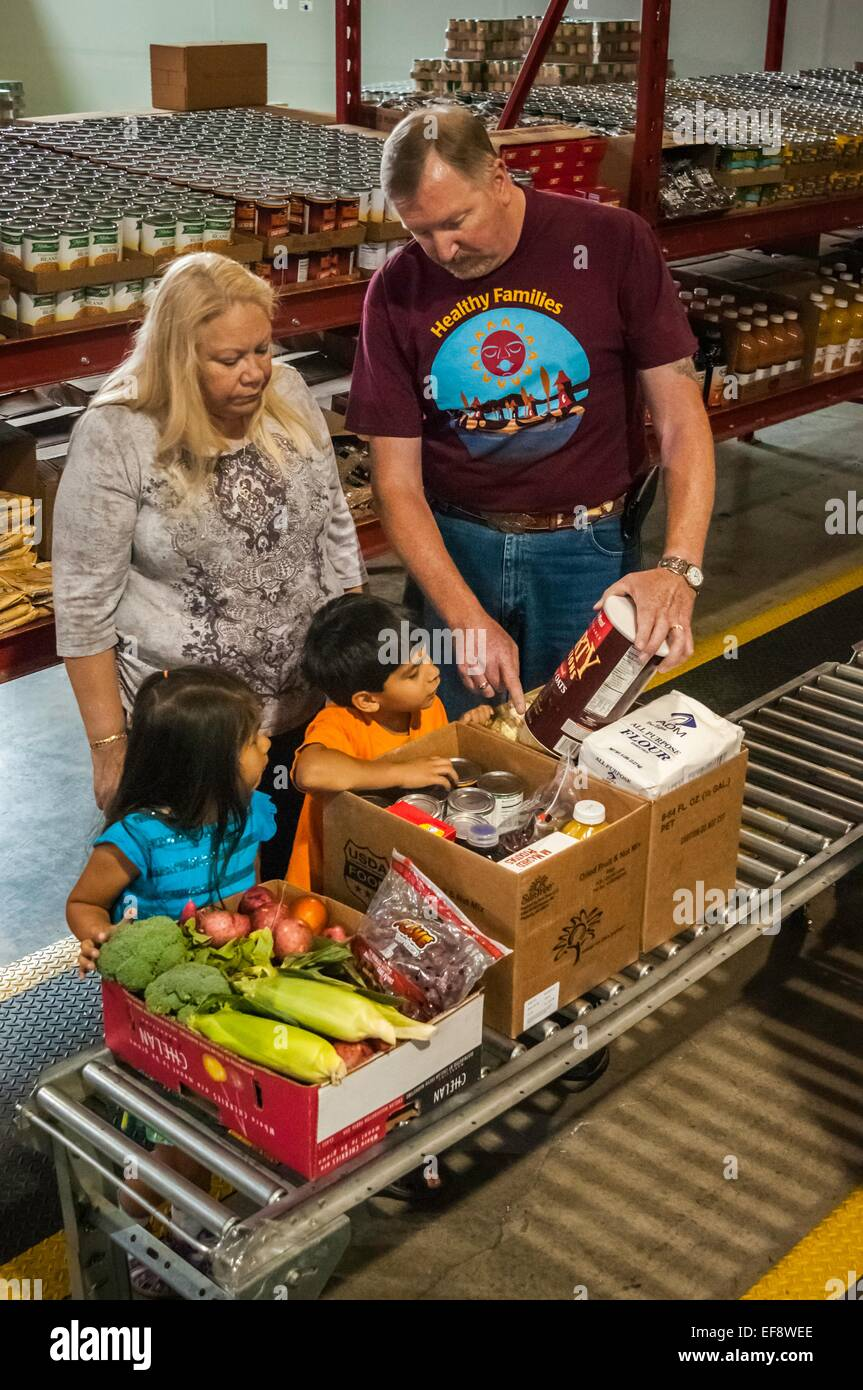 A family packs food provided by the Food Distribution Program on Indian Reservations at the food distribution center - Stock Image