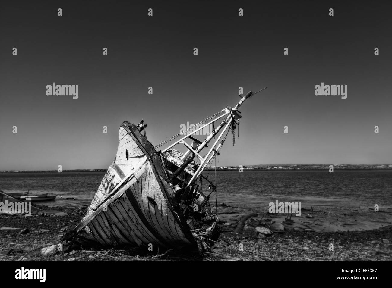 Beyond the need for repair, and old fishing boat sits broken, no longer used for fishing or tourist visits. - Stock Image