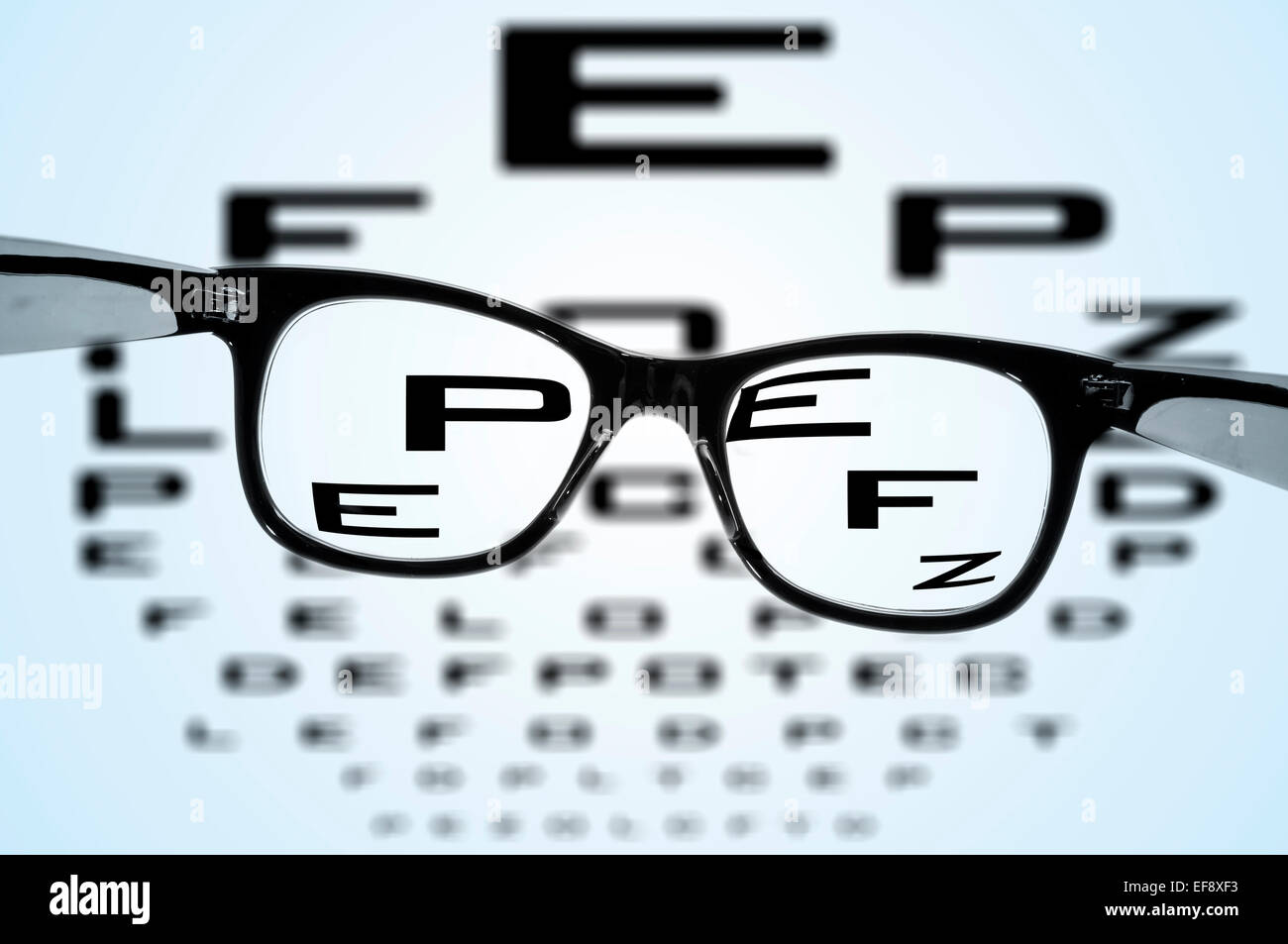 eyeglasses over a blurry eye chart - Stock Image
