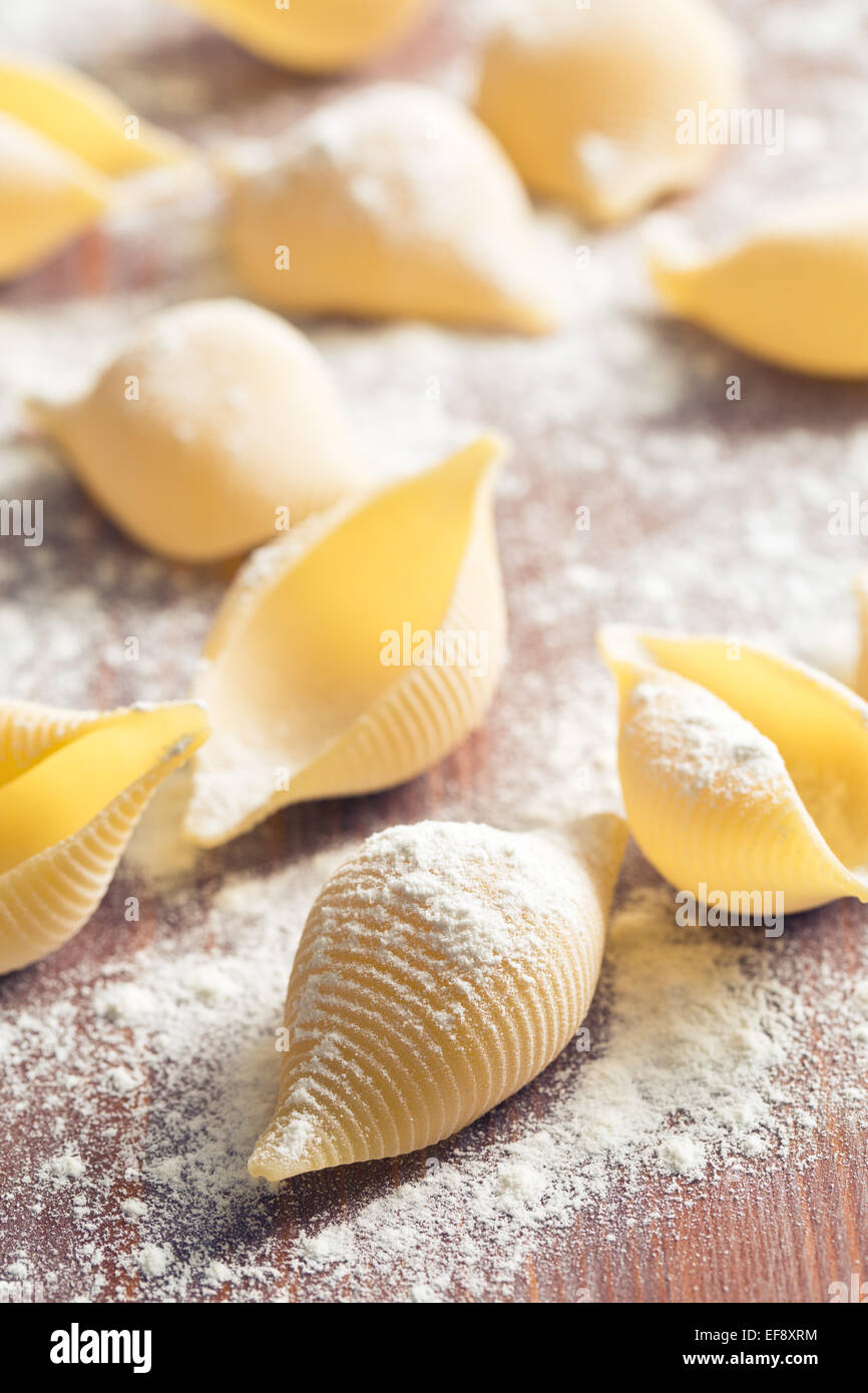 raw pasta and flour on table - Stock Image