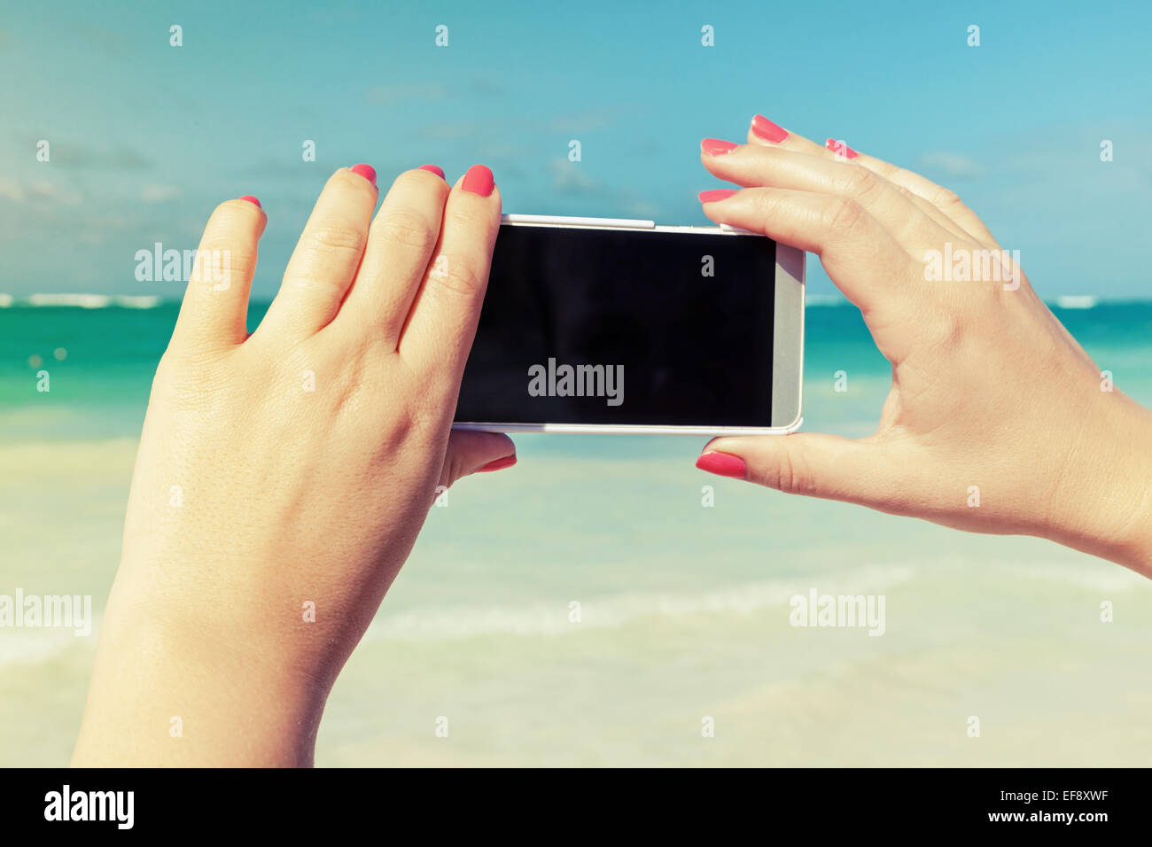 Woman using smart phone for taking outdoor photo on a beach