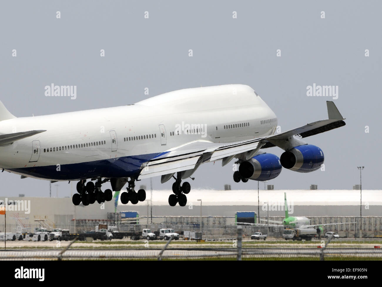 Heavy passenger jet landing at airport Boeing 747 - Stock Image