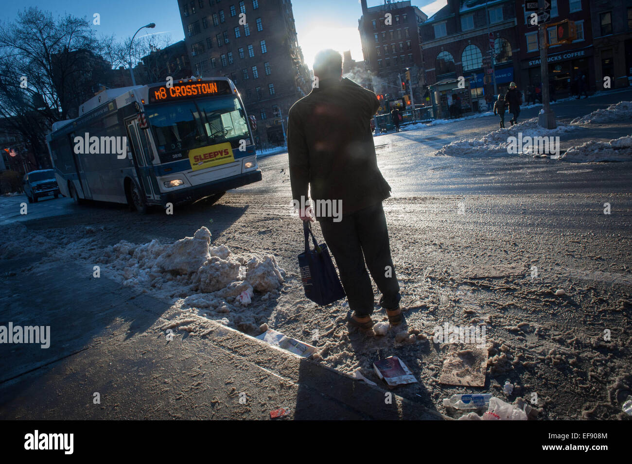 Jan. 28, 2015 - Manhattan, New York, U.S. - A commuter hails a crosstown bus in the West Village following the snowstorm - Stock Image