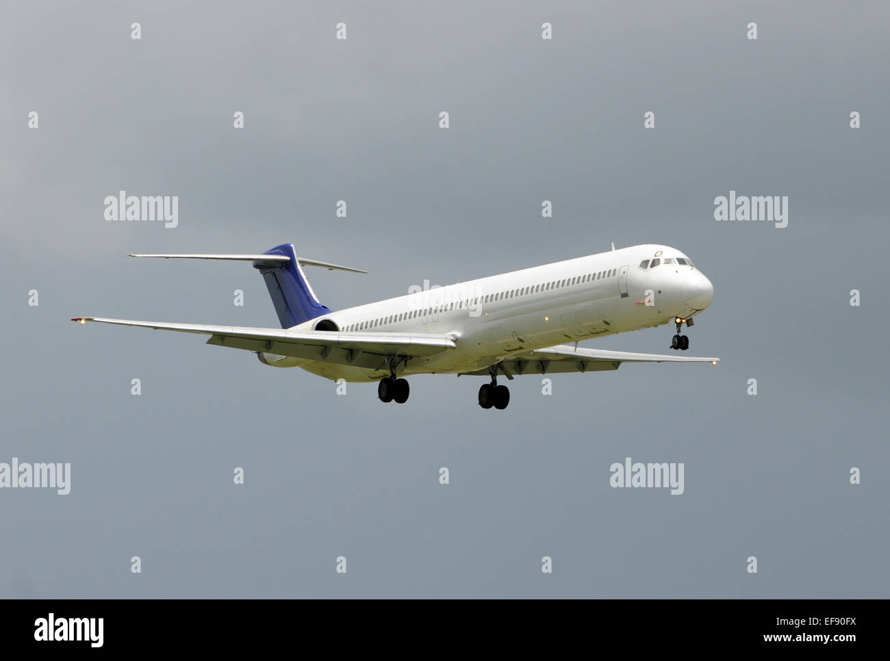 Jet airplane approaching airport for landing - Stock Image