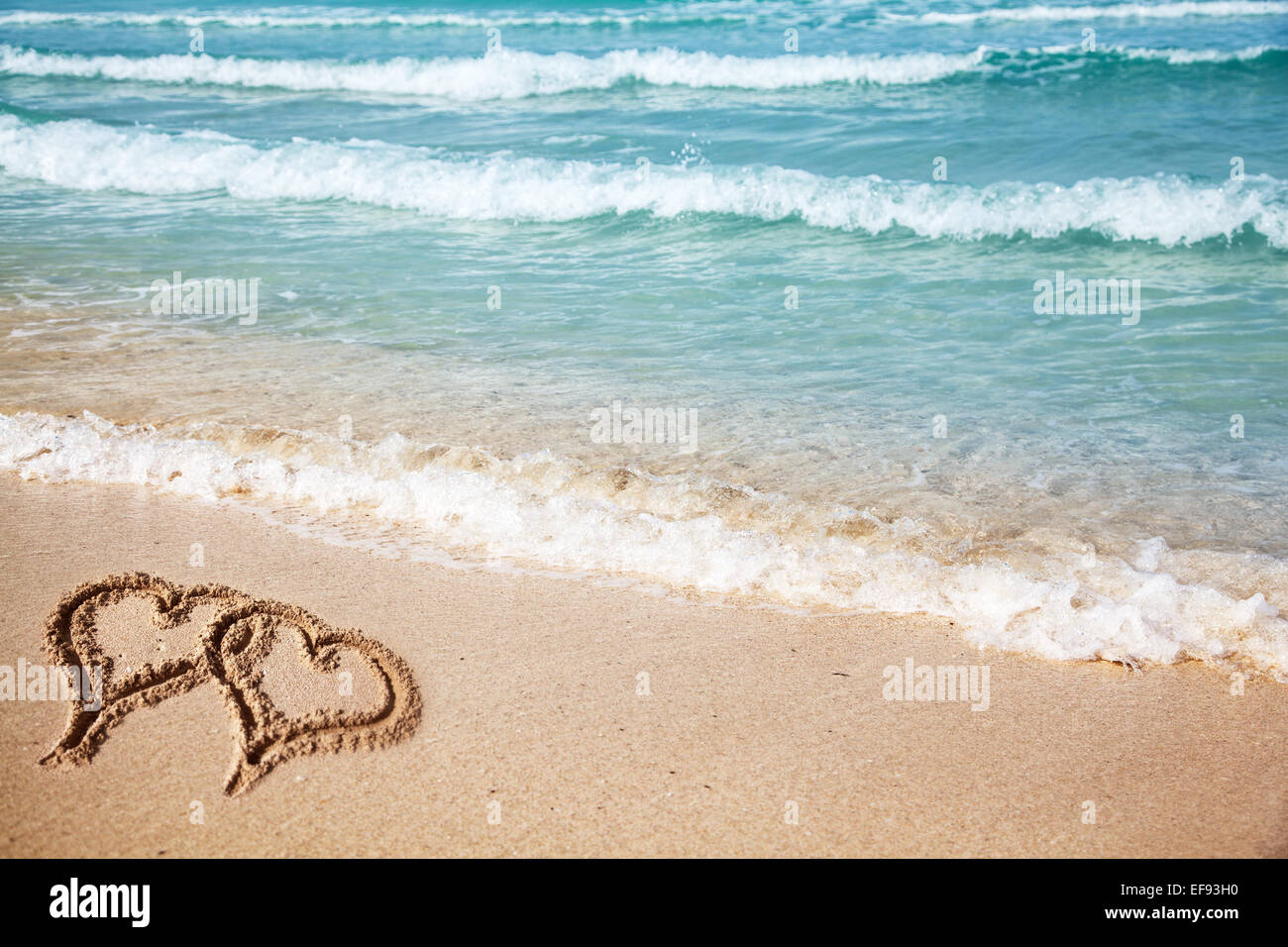 Hearts drawn on the beach sand. - Stock Image