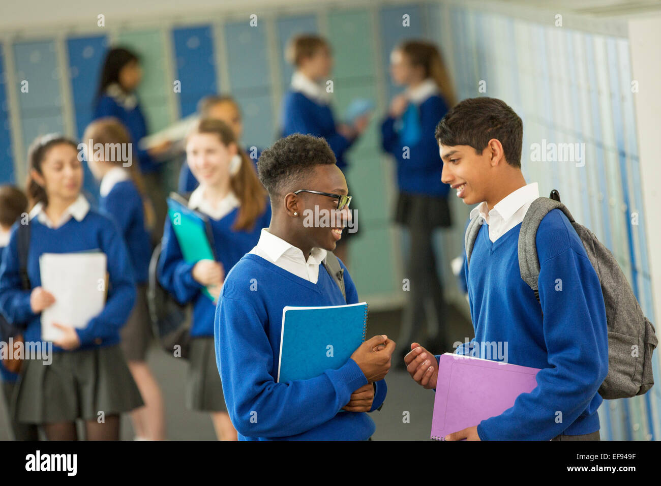 Two male students wearing school uniforms talking in locker room Stock Photo