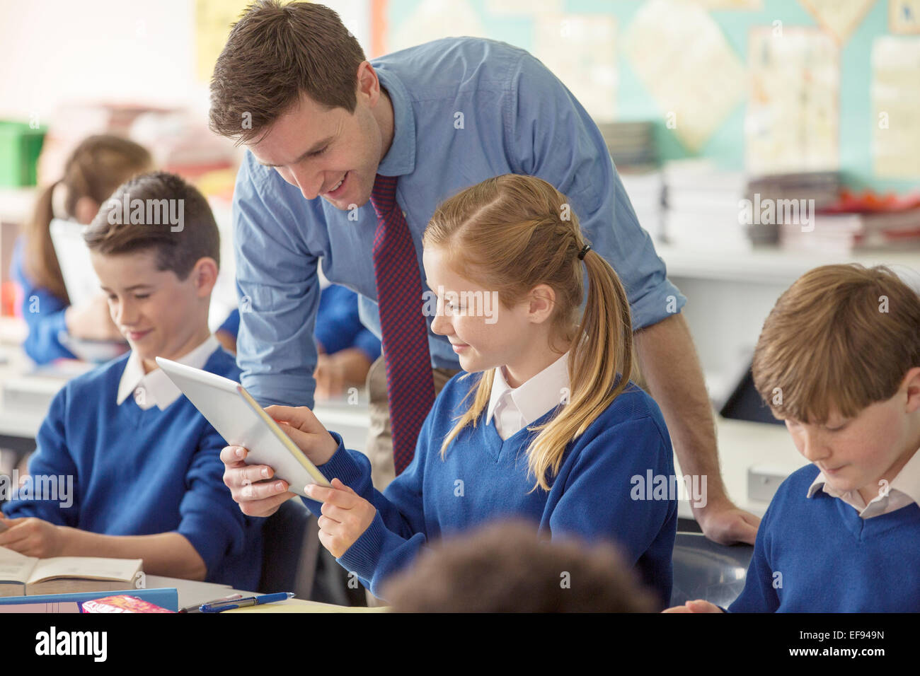 Teacher with his pupils in classroom using tablet pc - Stock Image