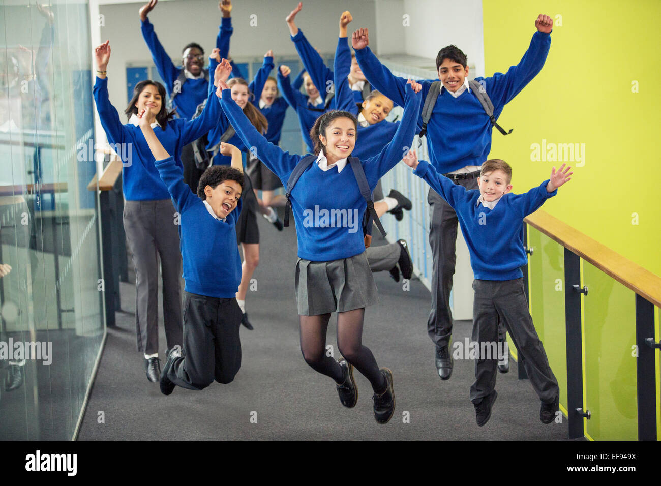 Enthusiastic high school students wearing school uniforms smiling and jumping in school corridor - Stock Image