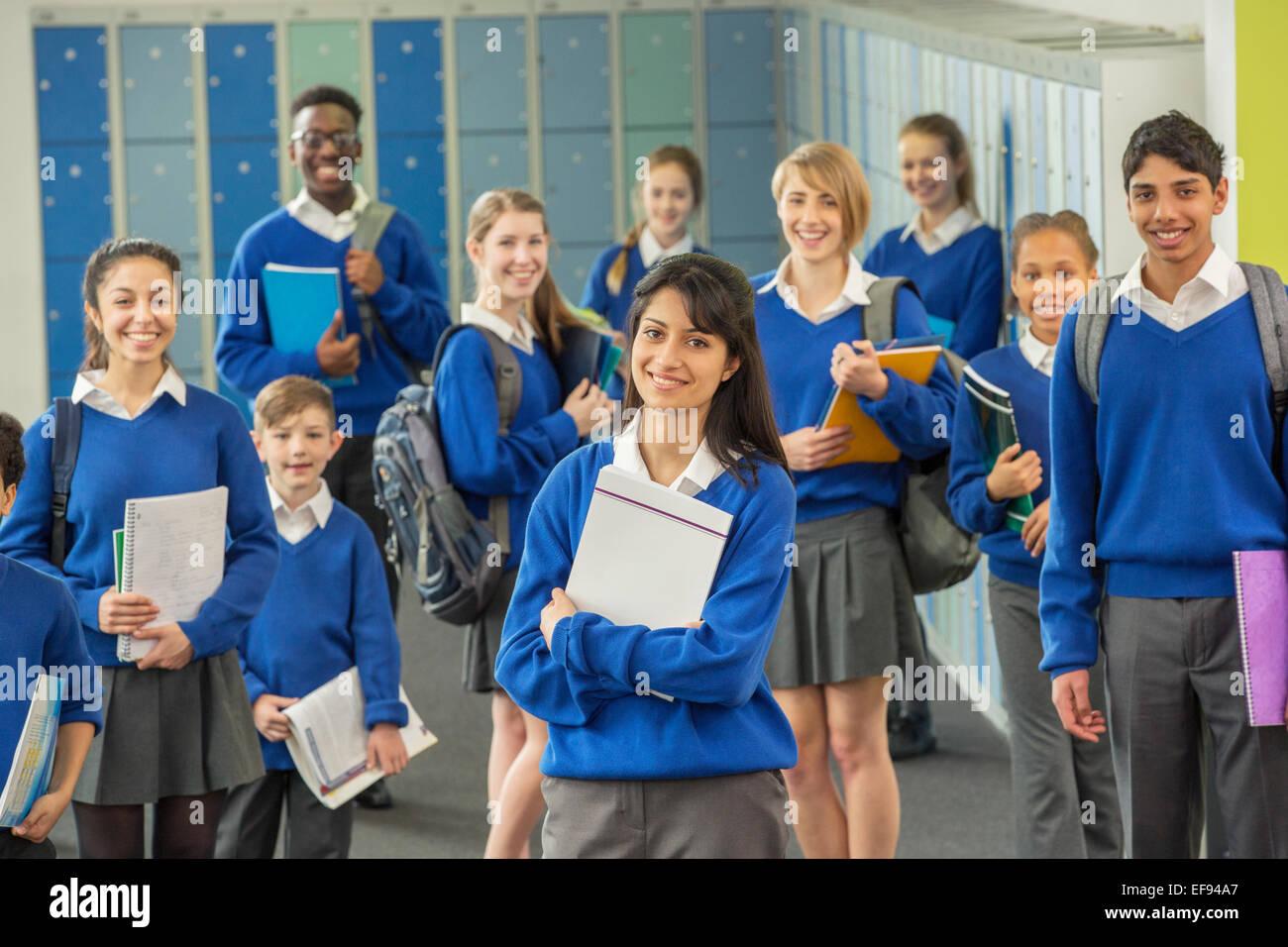 Group portrait of schoolchildren wearing school uniforms standing in corridor and smiling - Stock Image
