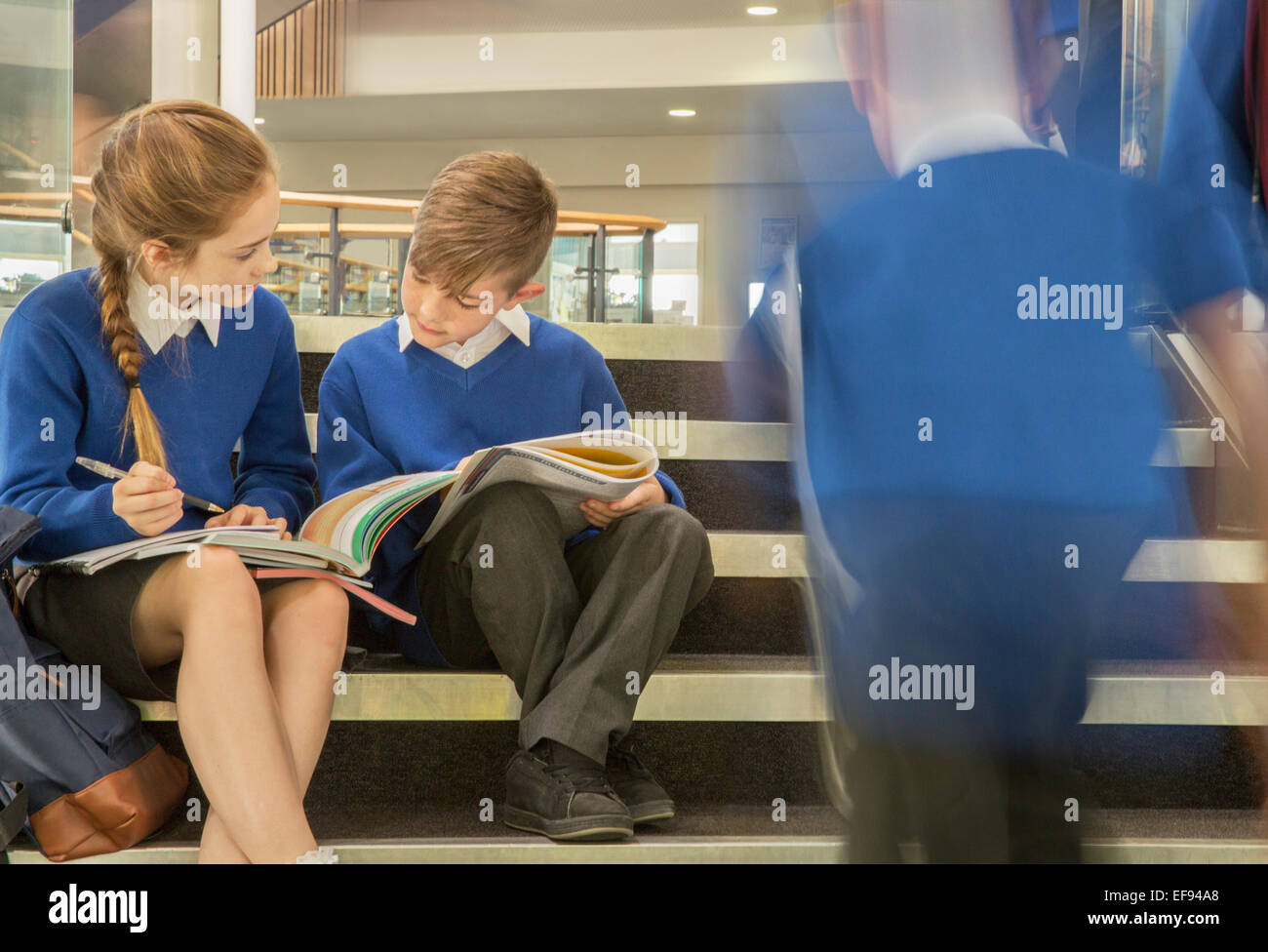 Elementary school children wearing school uniforms sitting on steps and writing in textbooks - Stock Image