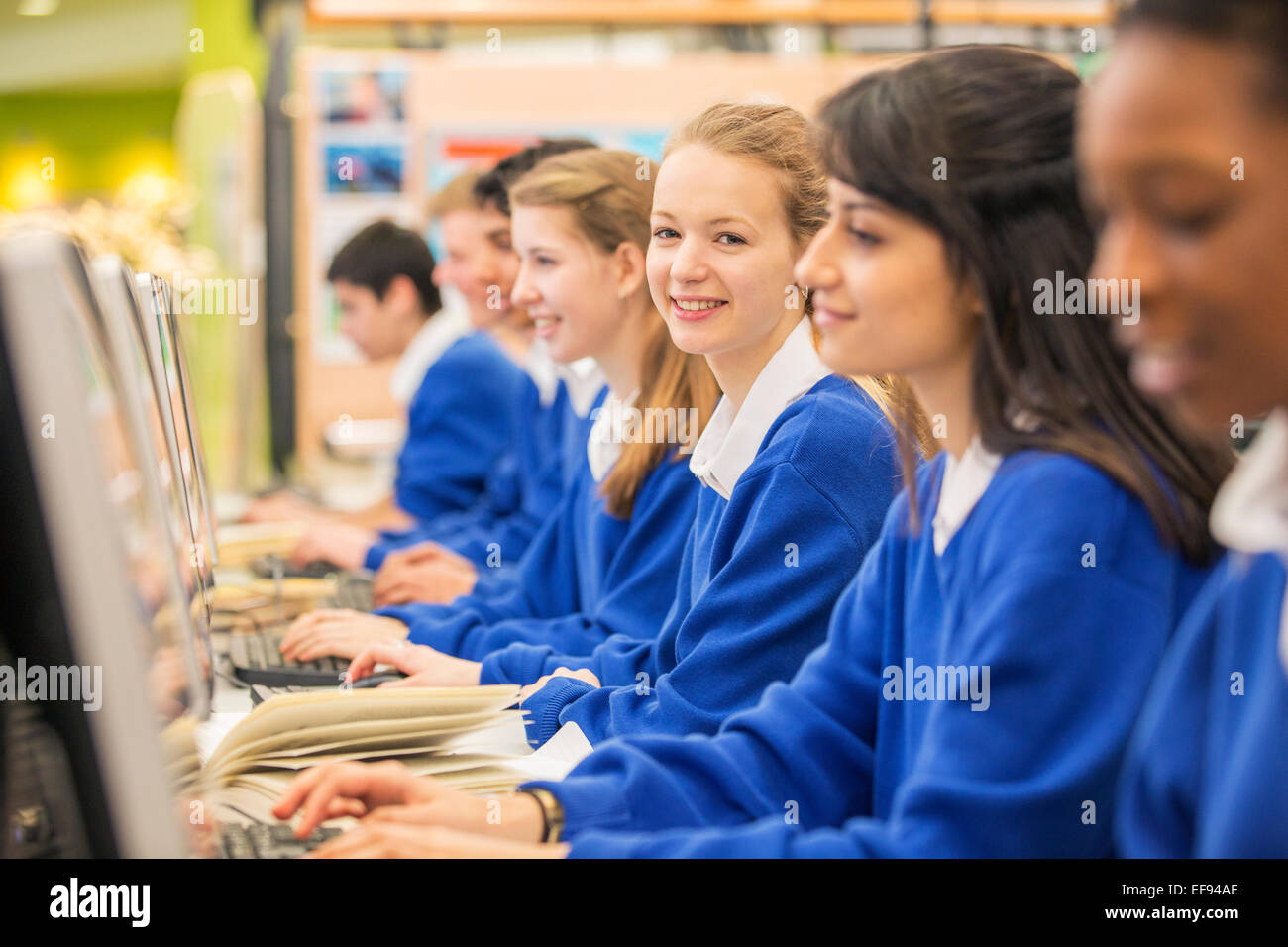 Students sitting in row during IT lesson - Stock Image