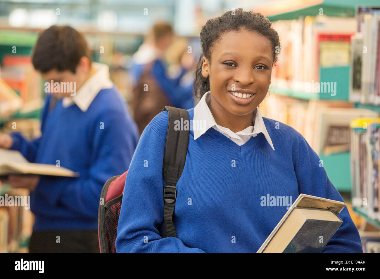 Portrait of smiling female student holding books in library - Stock Image