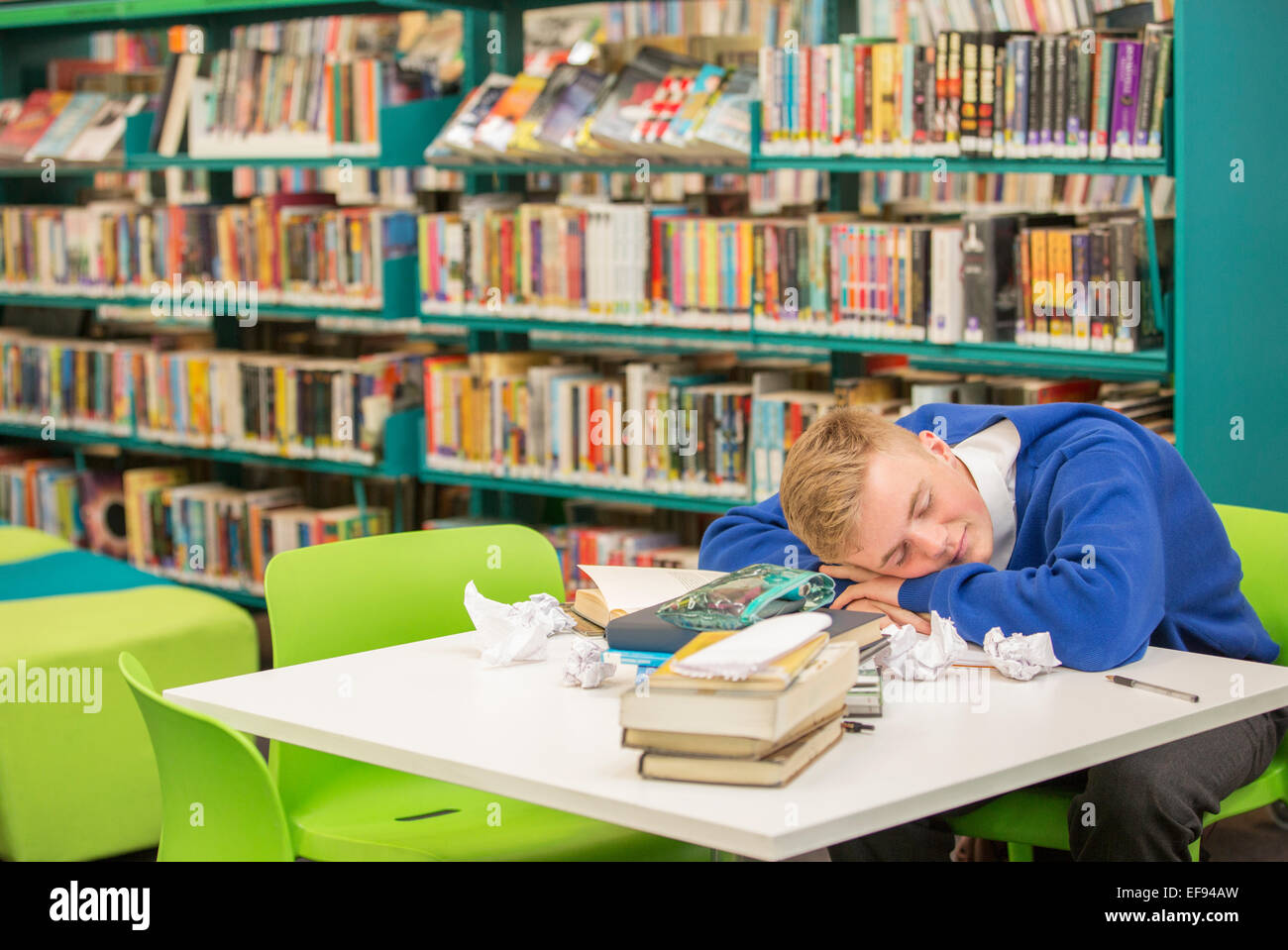 Exhausted student sleeping on table in library - Stock Image