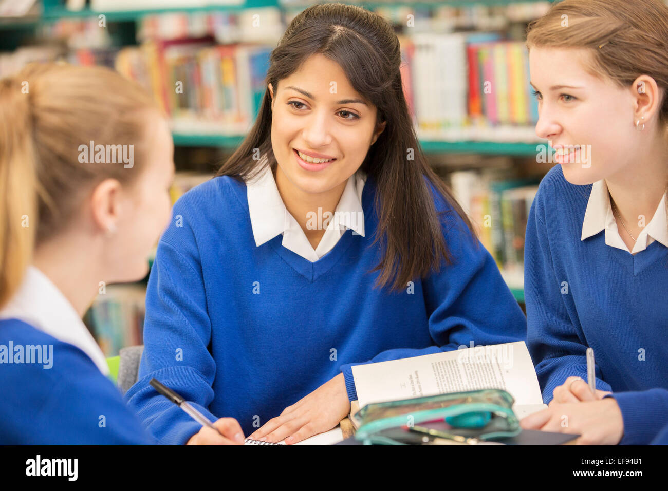 Three female students sitting in library and smiling - Stock Image