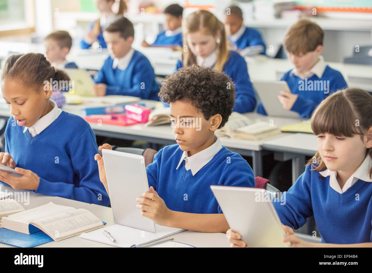 Elementary school children with digital tablets in classroom - Stock Image