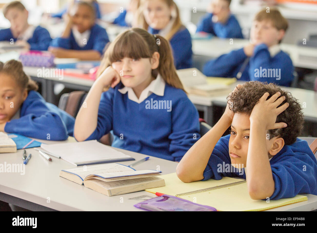 Elementary school children bored in classroom - Stock Image