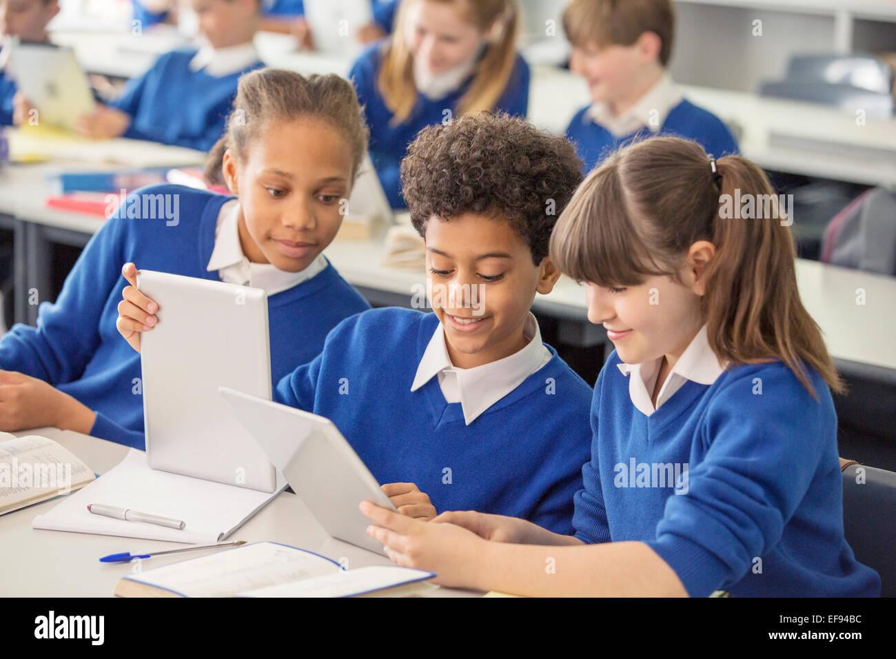 Elementary school children wearing blue school uniforms using digital tablets at desk in classroom Stock Photo