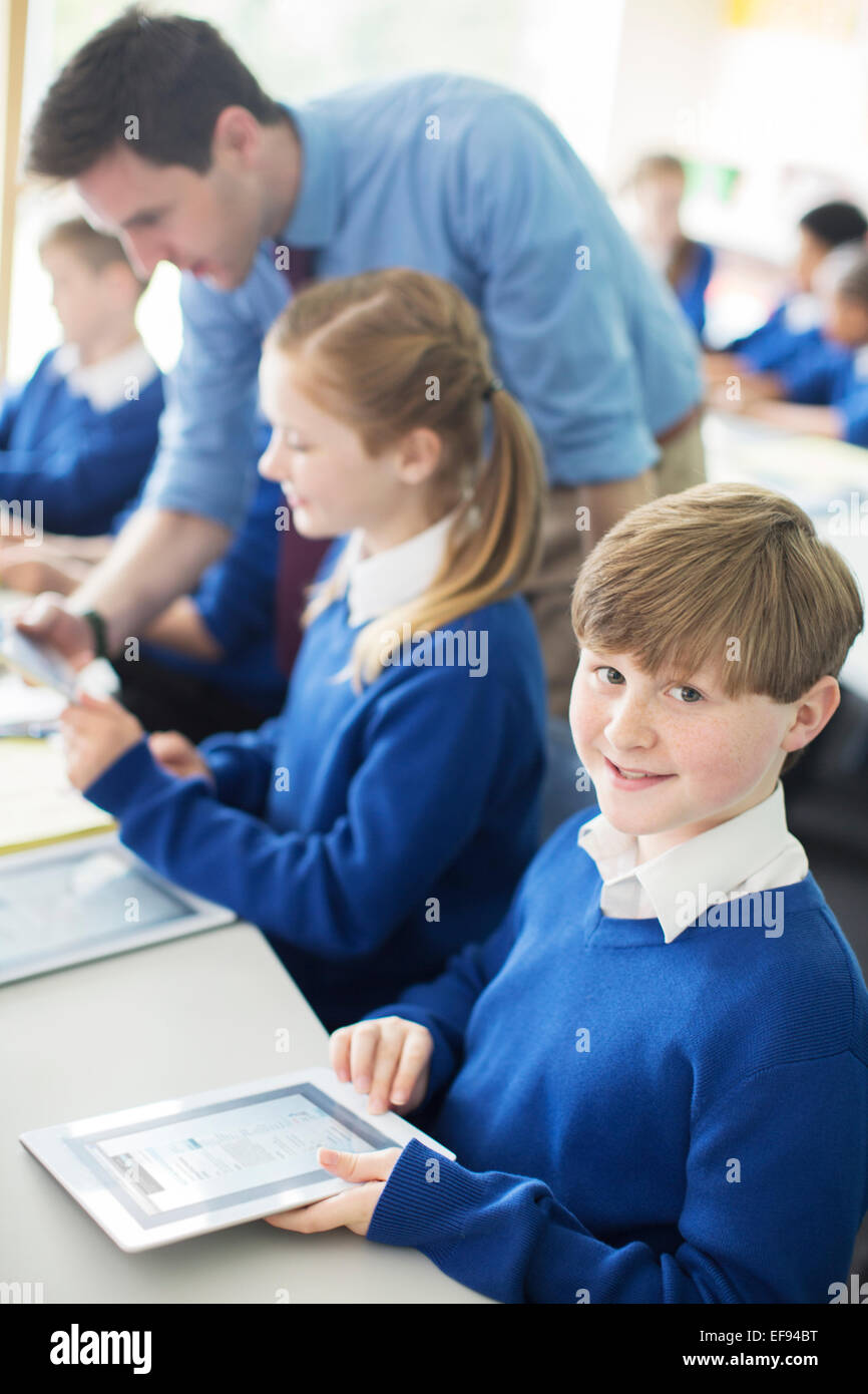 Portrait of schoolboy sitting with digital tablet in classroom, children and teacher in background - Stock Image