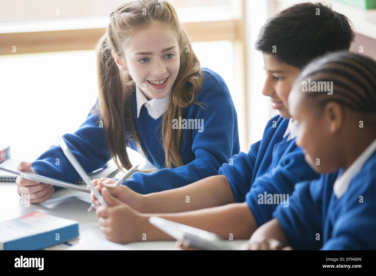 Pupils using tablet pc's in classroom Stock Photo