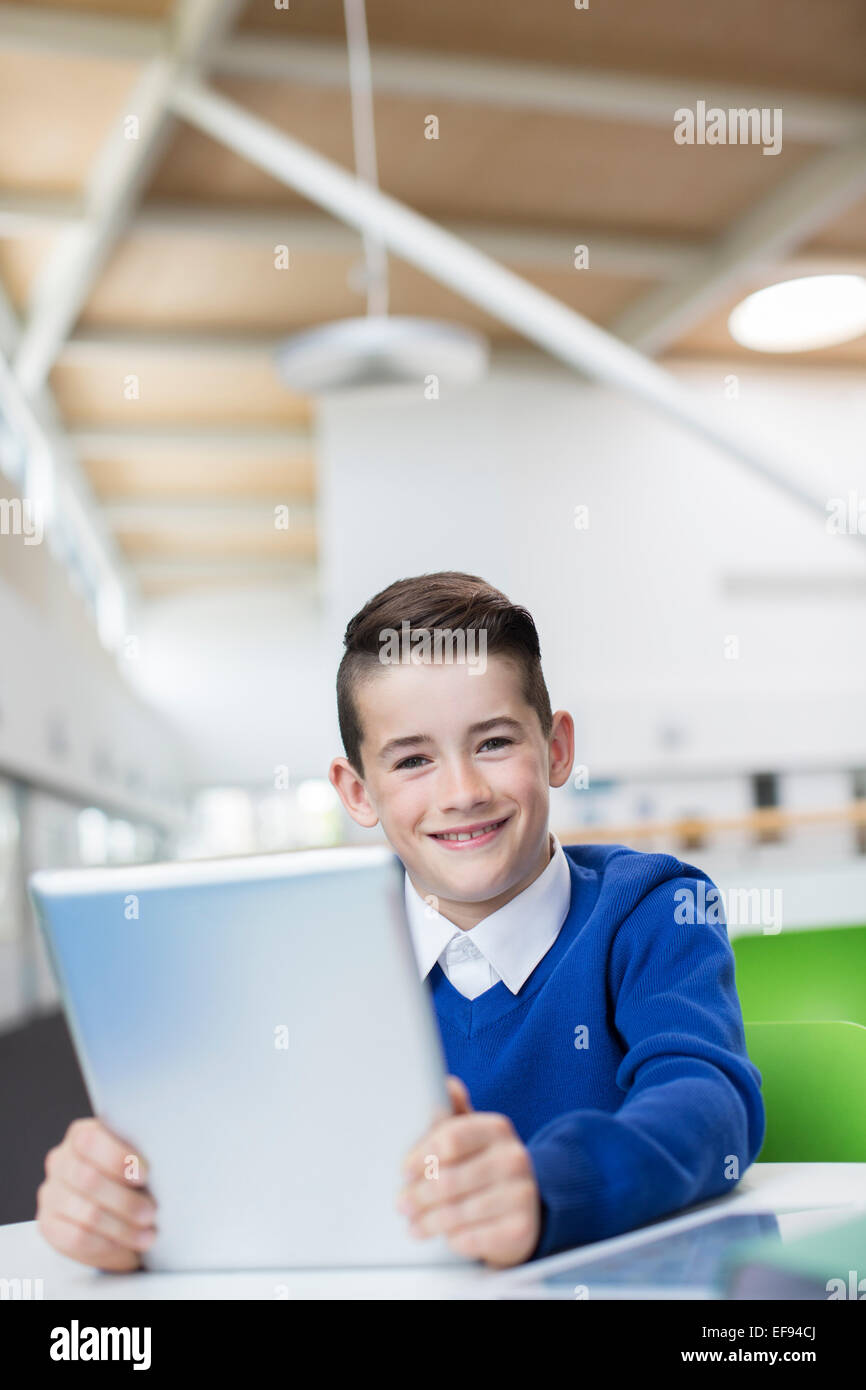 Portrait of smiling schoolboy with tablet pc - Stock Image