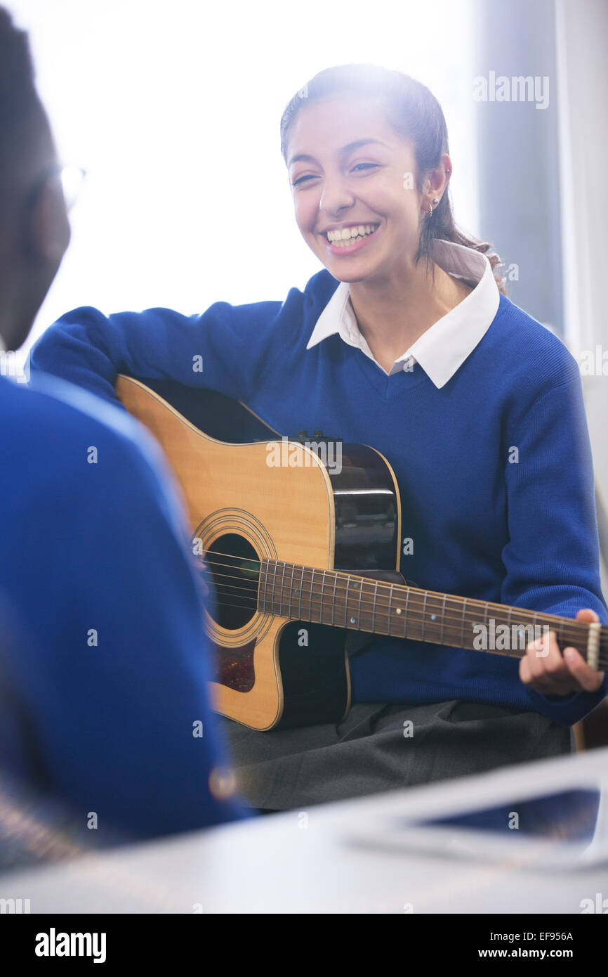 Smiling female student playing acoustic guitar Stock Photo