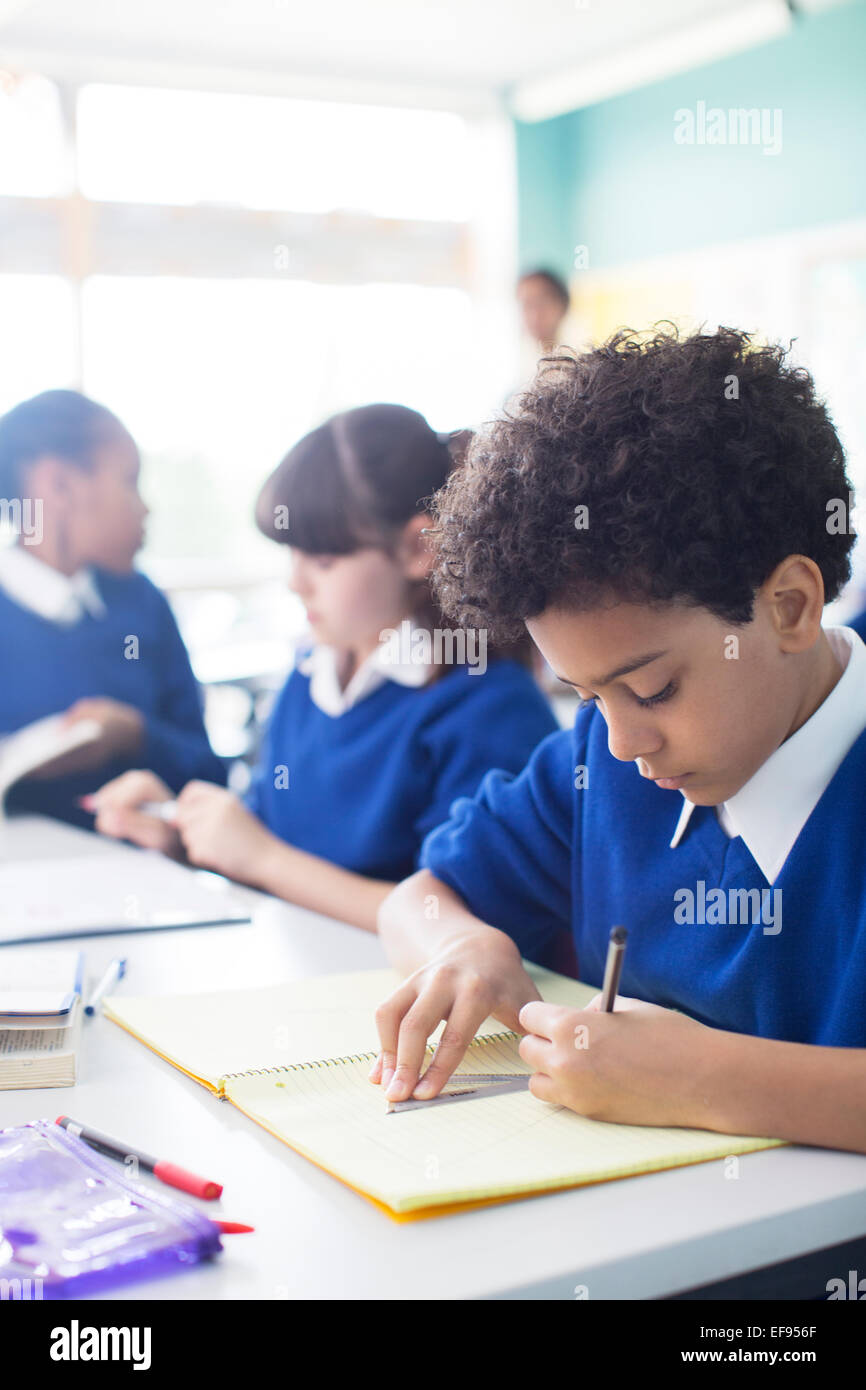 Schoolboy drawing in notebook at desk in classroom, girls in background - Stock Image