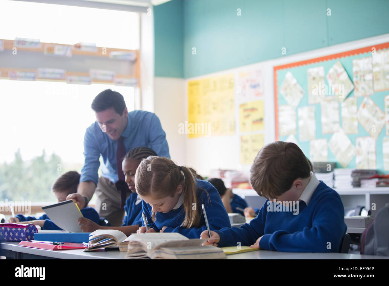 Male teacher assisting elementary school children in classroom during lesson - Stock Image