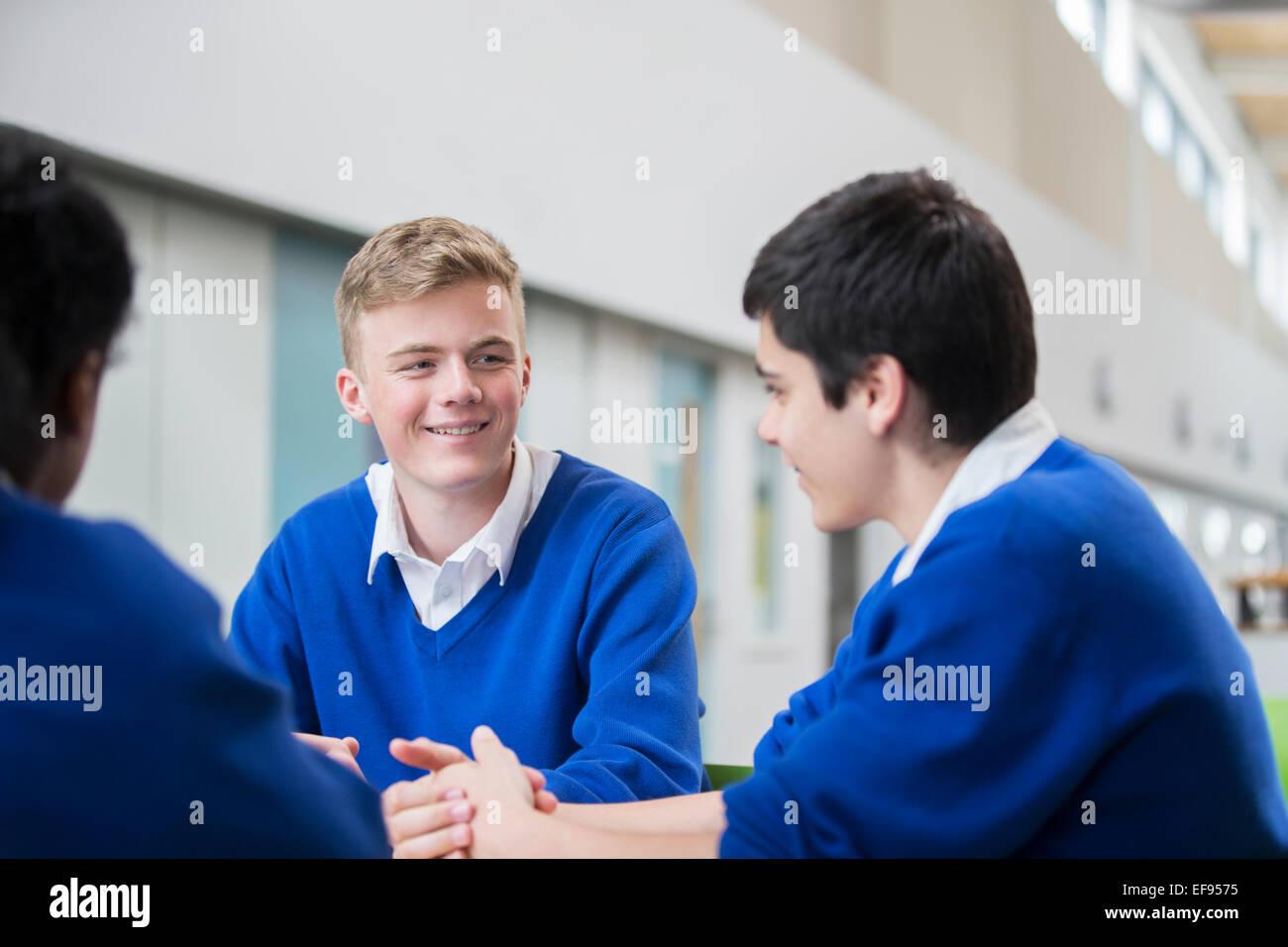 Three male students wearing blue school uniforms talking in corridor - Stock Image
