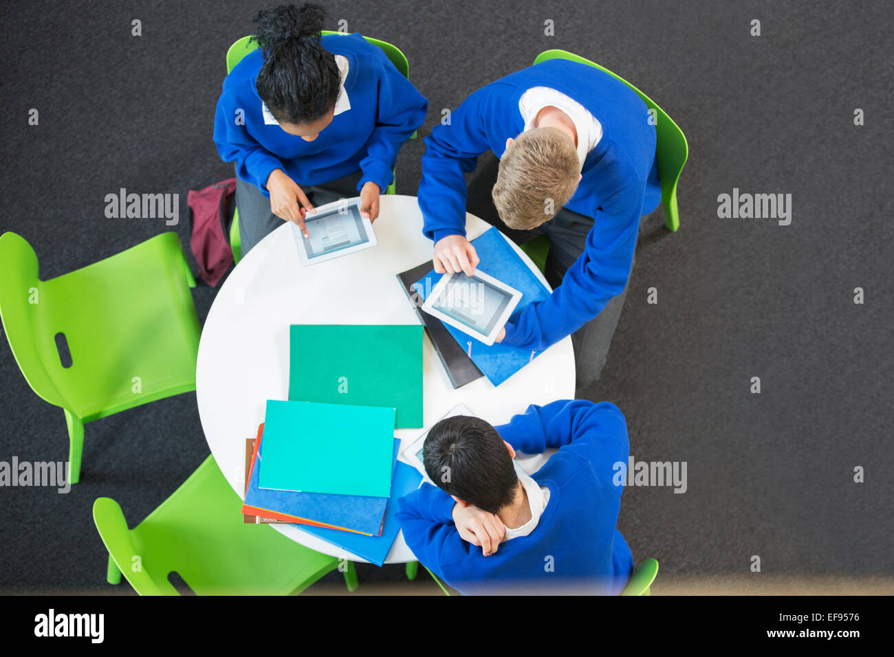 Overhead view of three students with digital tablets at round table Stock Photo