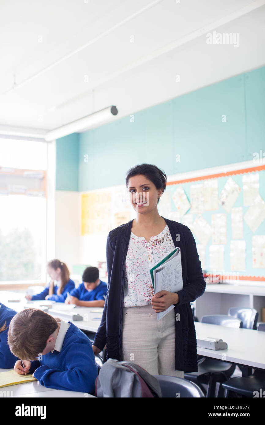 Portrait of smiling female teacher and elementary school children in classroom - Stock Image