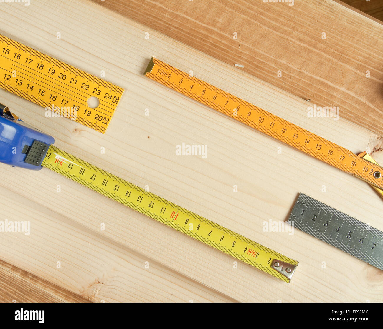 Rulers on a wooden background. - Stock Image