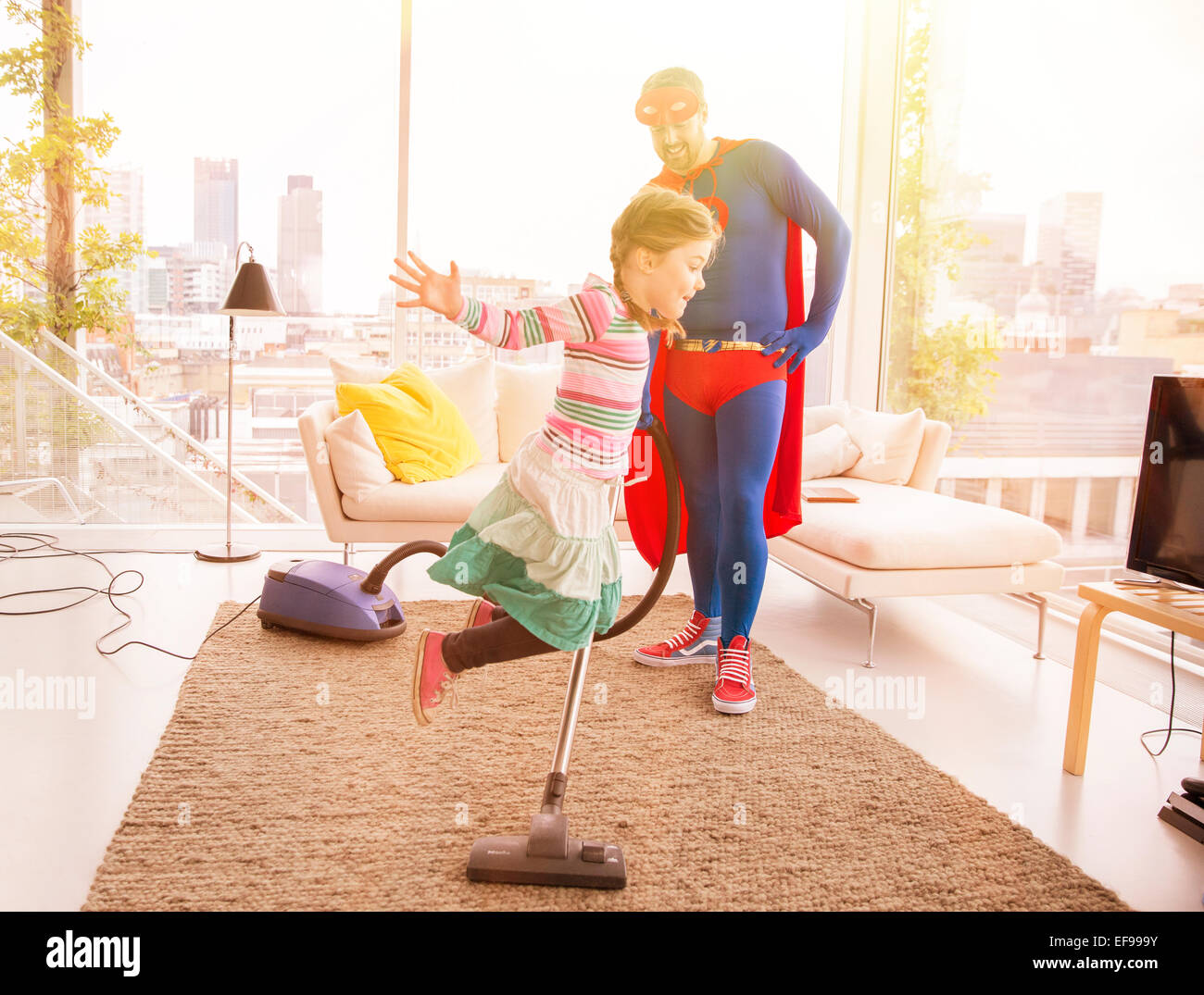 Superhero father vacuuming while daughter jumps in living room - Stock Image