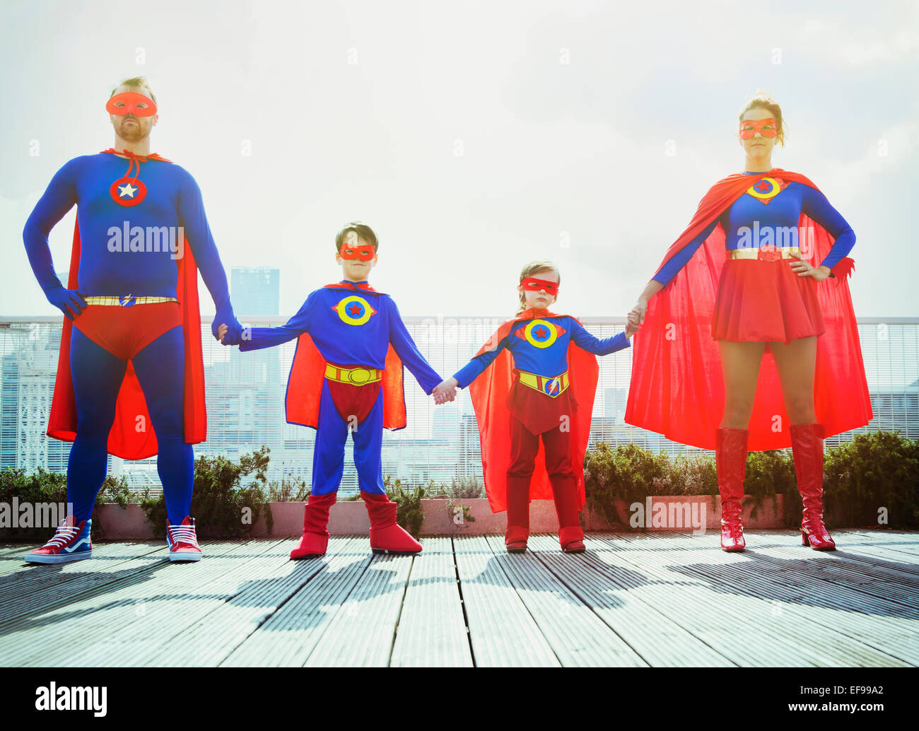Superhero family holding hands on city rooftop - Stock Image