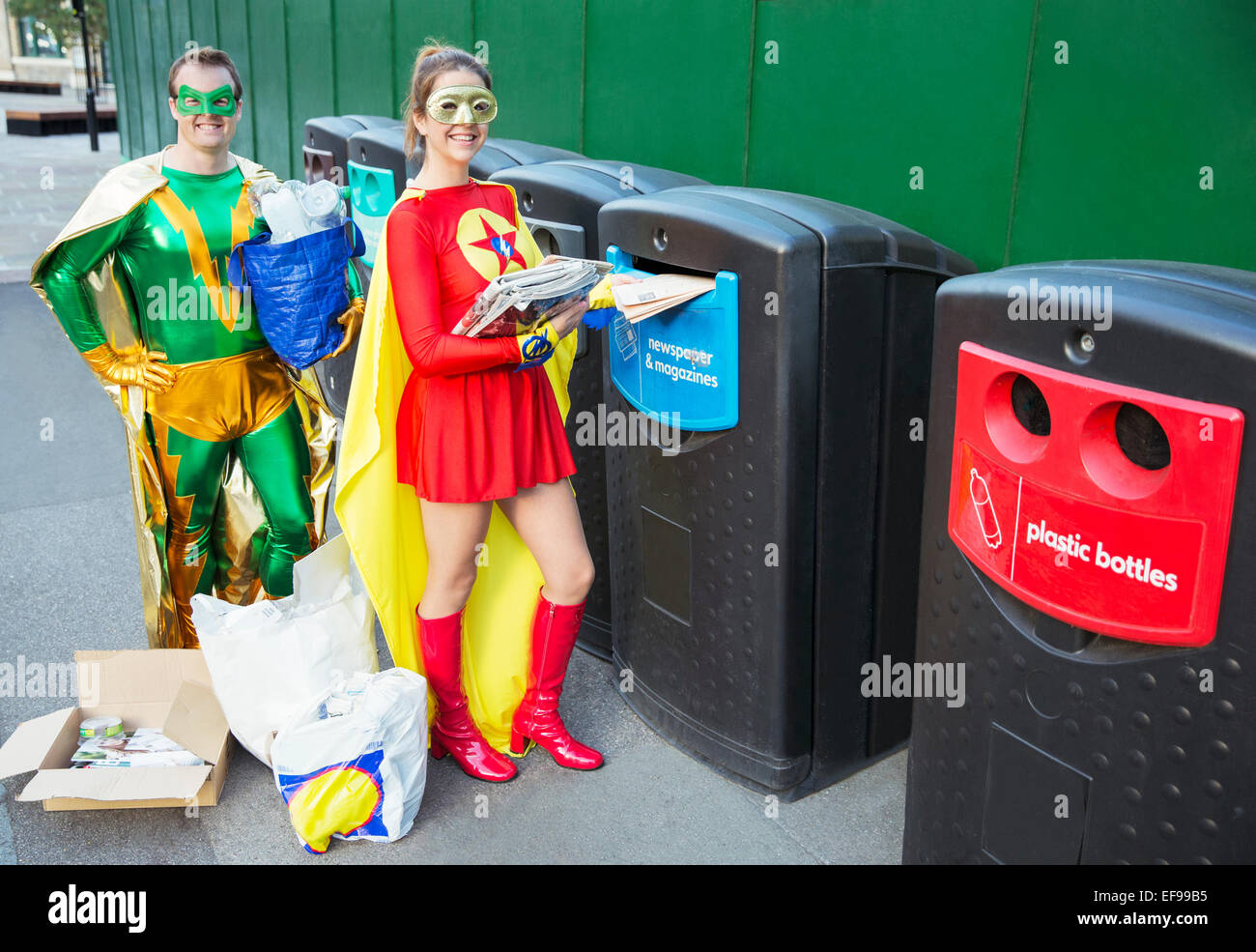 Superhero couple recycling on city sidewalk - Stock Image