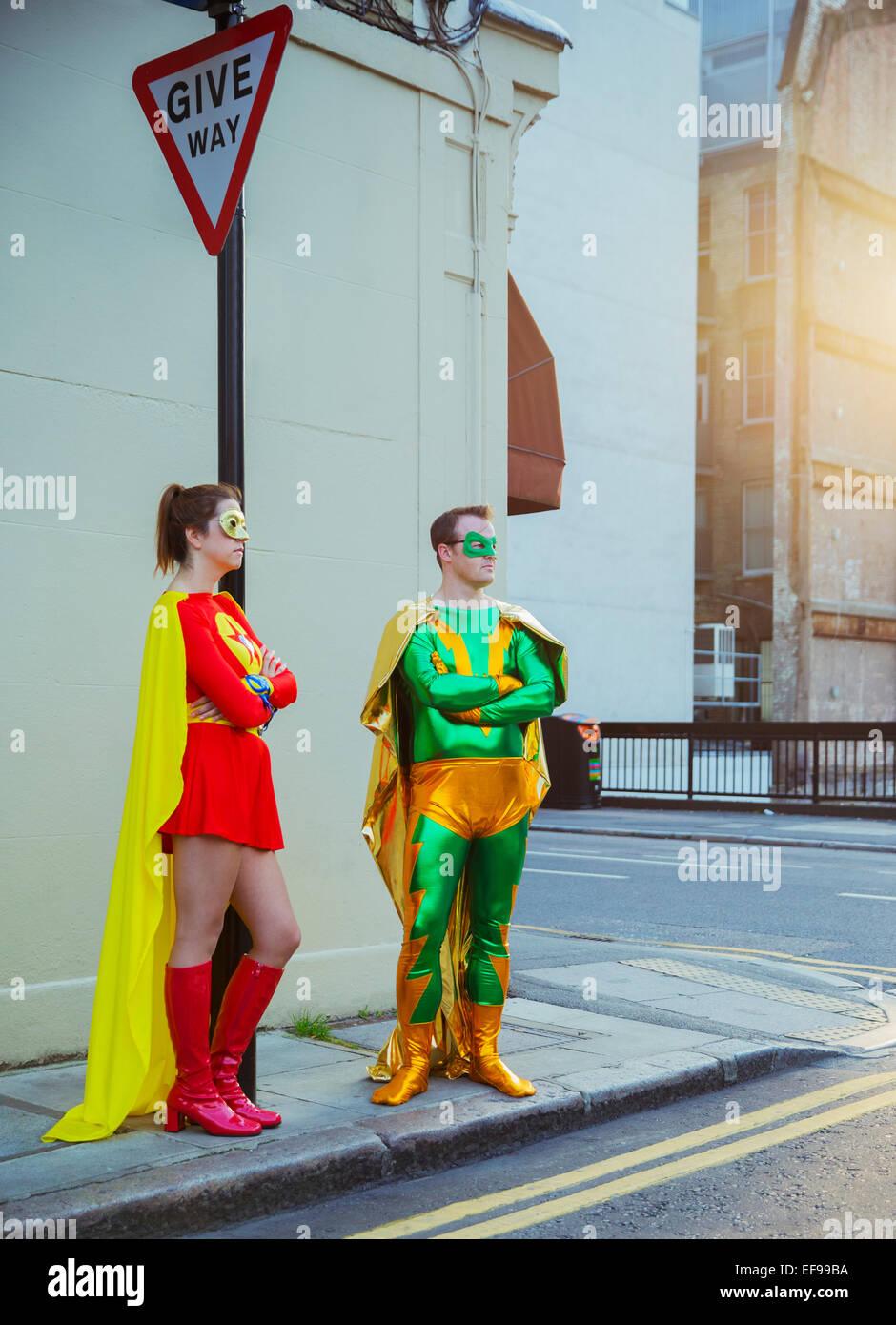 Superhero couple waiting at corner on city sidewalk - Stock Image