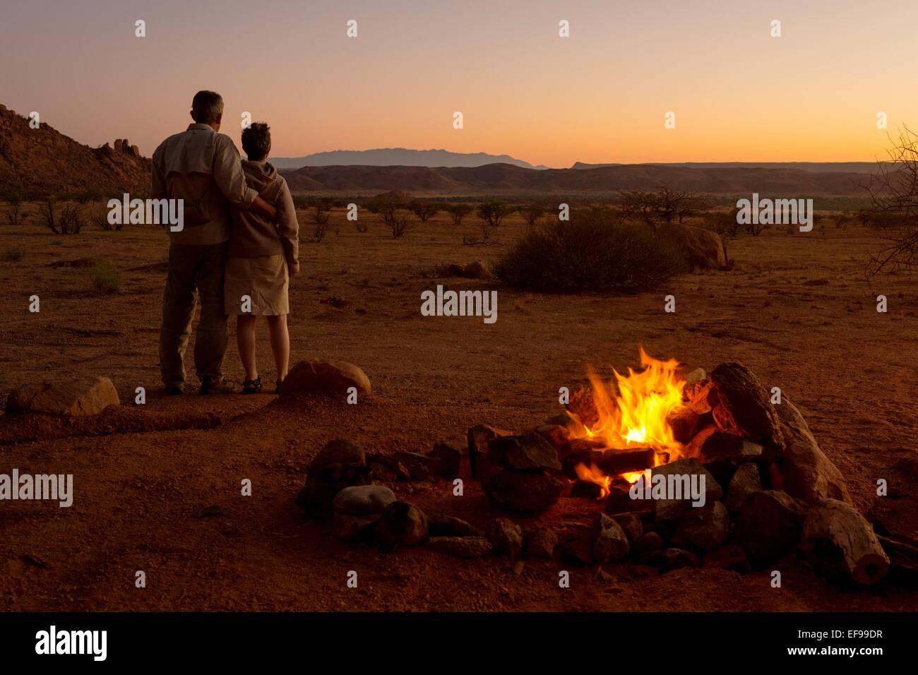 A romantic shot of a couple enjoying the setting sun at Mowani Mountain Camp, Damaraland, Namibia, beside their - Stock Image