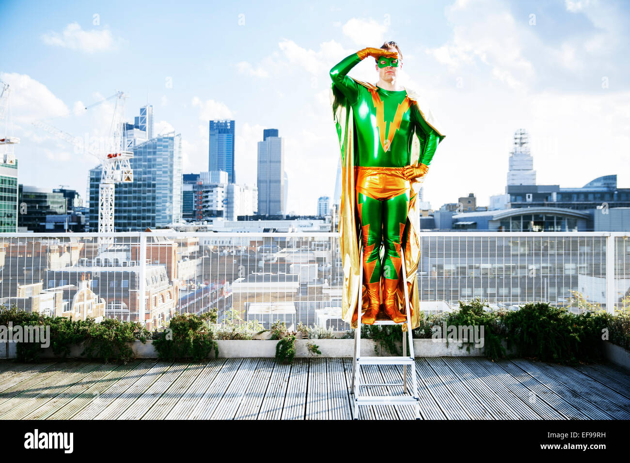 Superhero overlooking view from stepladder on city rooftop - Stock Image