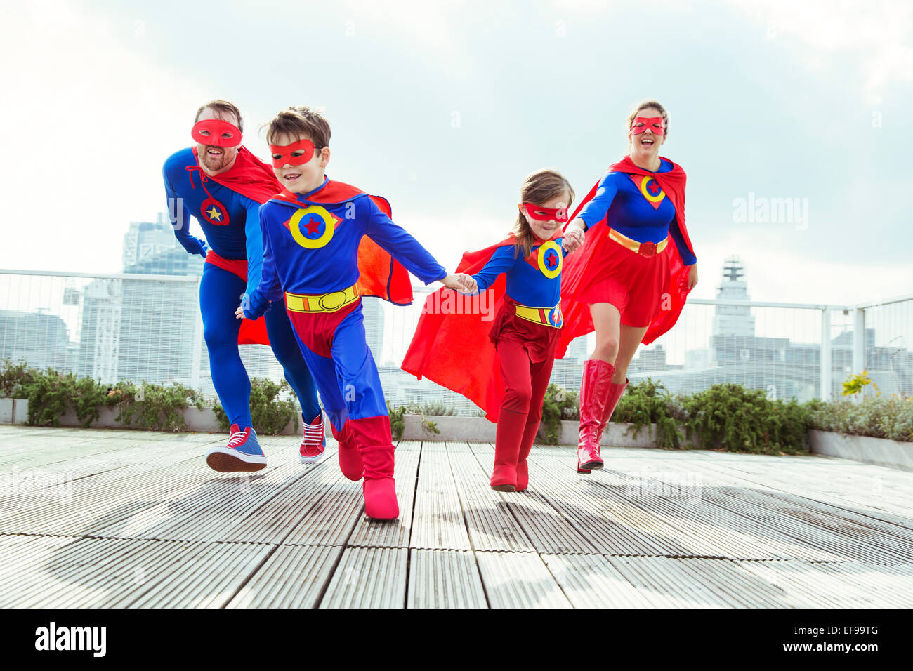 Superhero family playing on city rooftop - Stock Image