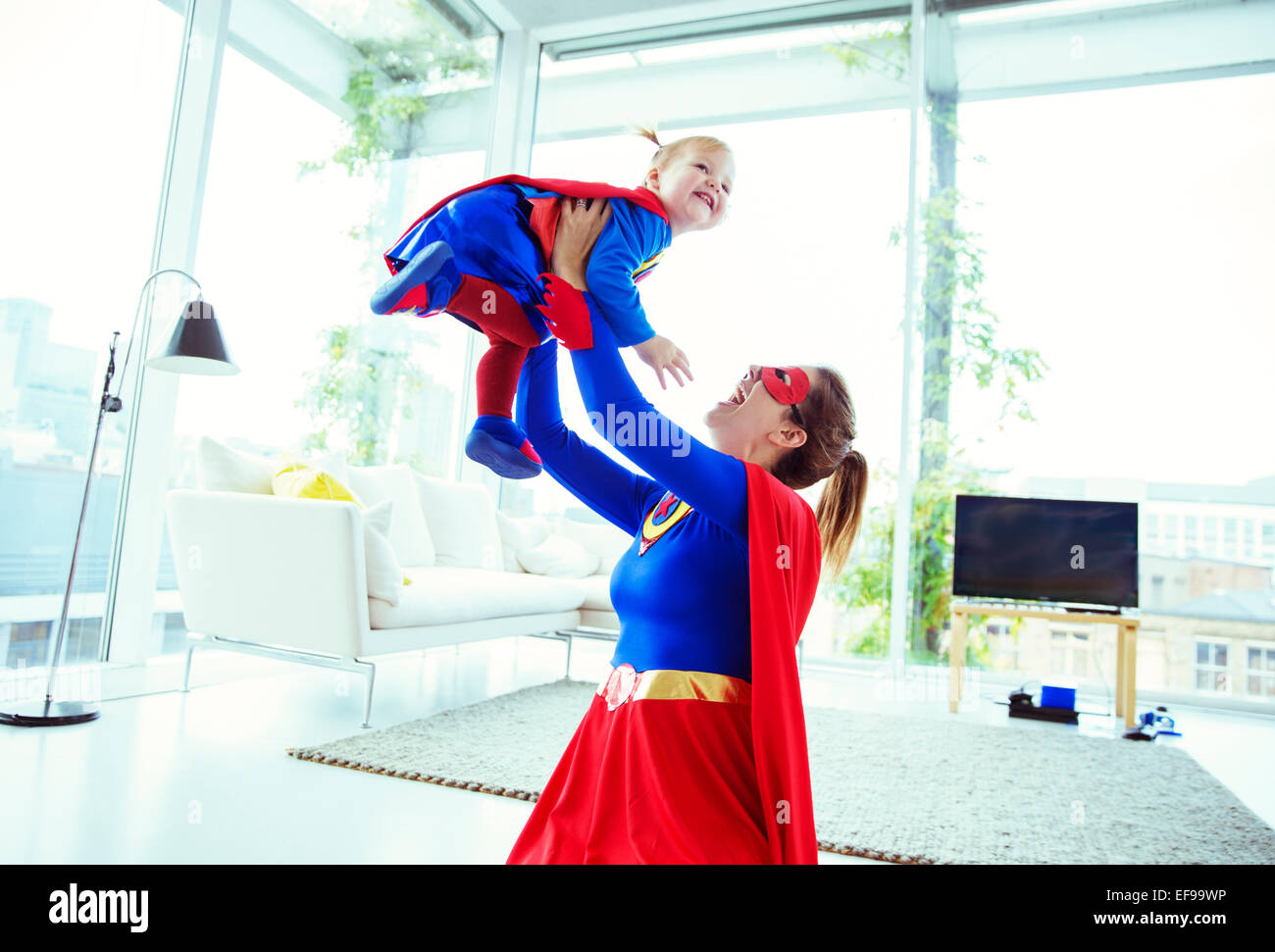 Superhero playing with baby in living room Stock Photo