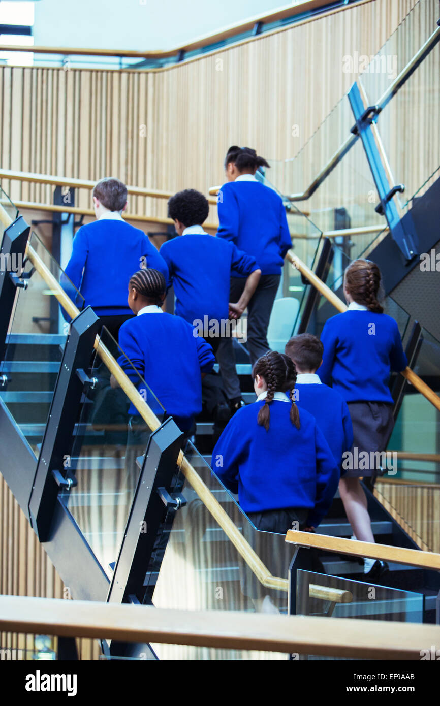 Rear view of group of pupils wearing blue school uniforms walking up stairs in school - Stock Image