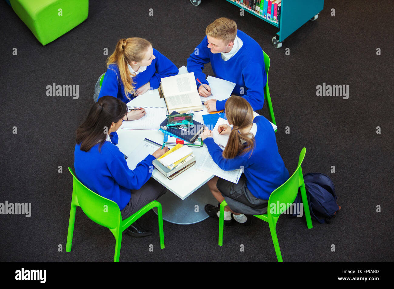 Overhead view of four students doing their homework at round table - Stock Image