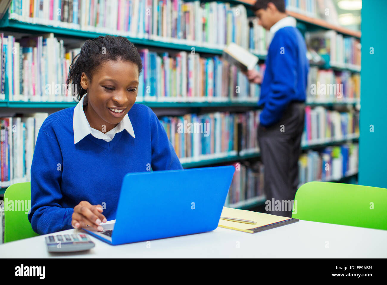 Smiling female student using laptop in library - Stock Image